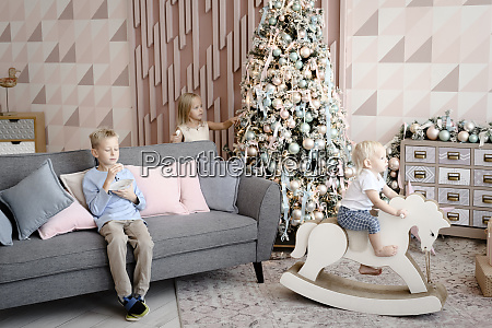 three children playing and eating cookies