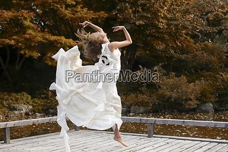 ballerina wearing white dress and jumping