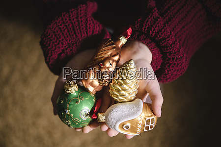 various christmas ornaments in girls hand