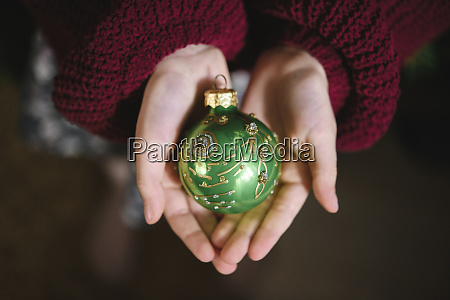 green christmas ornament in girls hand