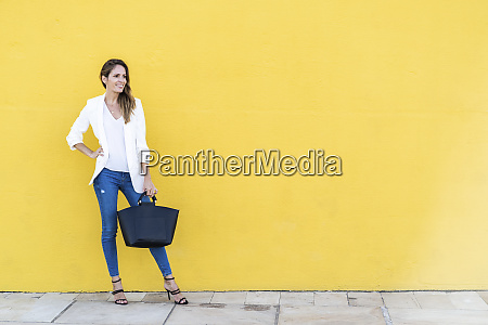 smiling woman standing at a yellow