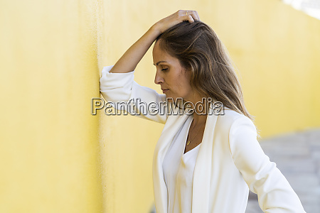 desperate woman leaning against a yellow