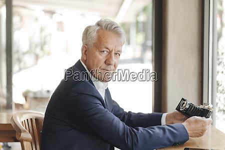 portrait of senior businessman holding old