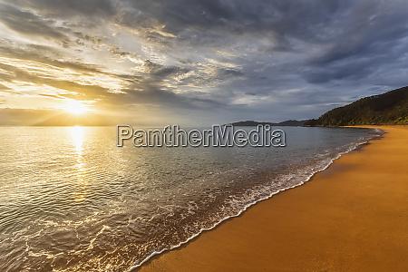 new zealand clouds over sandy coastal