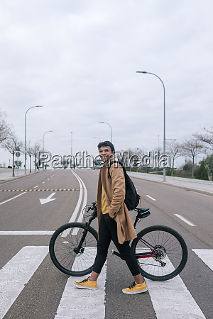 young man with bicycle crossing a