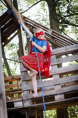 superhero girl playing in a tree