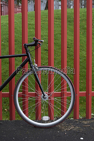 bicycle parked on road by fence