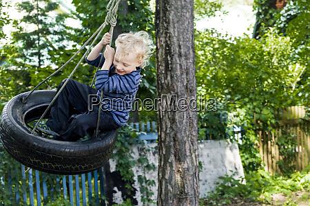 little boy sitting on tire swing