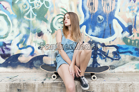 young woman sitting on skateboard in