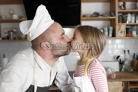 father and daughter cooking in the