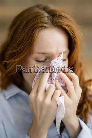 redheaded woman blowing nose