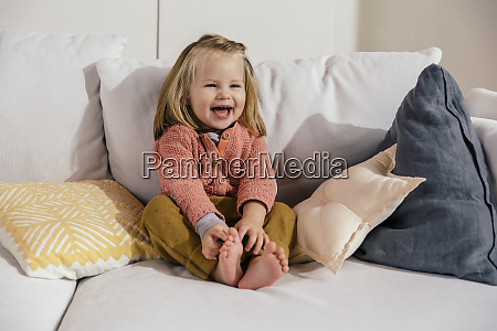 laughing little girl sitting on couch