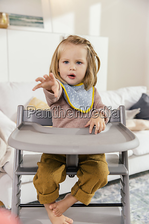 little girl sitting on high chair