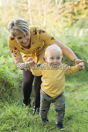 mother helping little son walking on