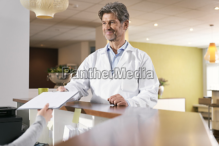 doctor taking medical record at reception