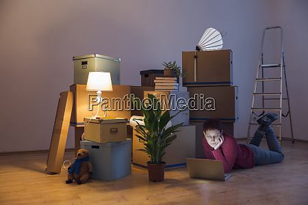 woman using laptop surrounded by cardboard