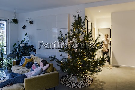 woman at home with decorated pine