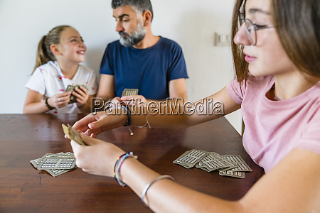 father with two daughters playing cards