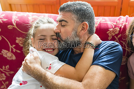 father hugging with daughter on couch