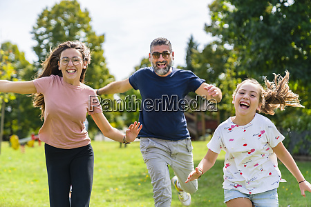 carefree father with two daughters running