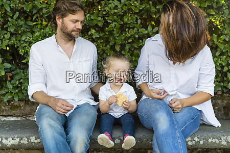 parents with happy little daughter sitting