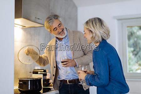 mature couple preparing dinner in kitchen