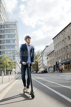 young businessman riding e scooter on
