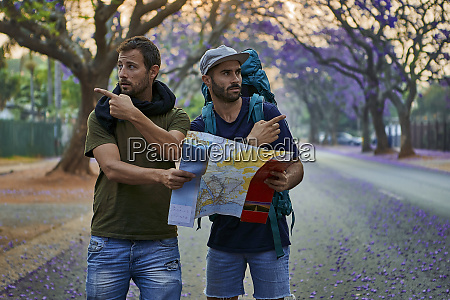 backpackers with map on a street
