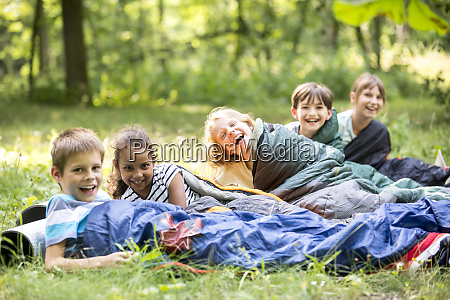 school children camping in forest lying