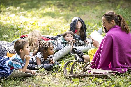 teacher reading story to school children