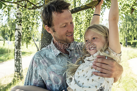 smiling father holding daughter hanging on