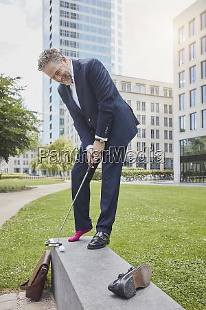mature businessman playing golf in the