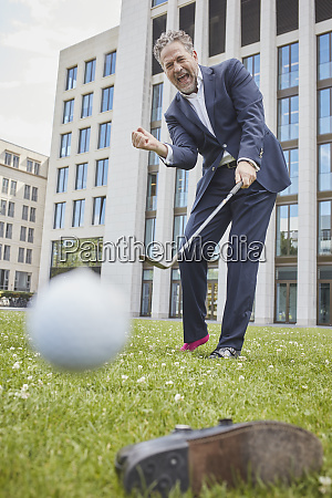 happy mature businessman playing golf on