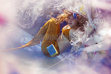 teenage mermaid girl surrounded by plastic