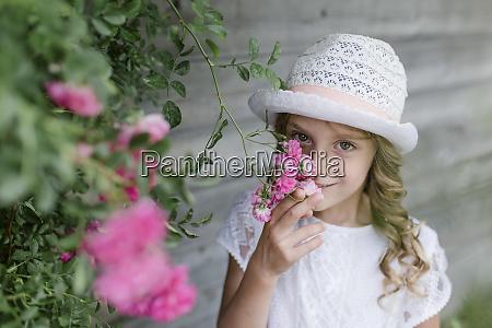 portrait of girl at rosebush smelling