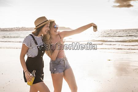 two girlfriends having fun walking on