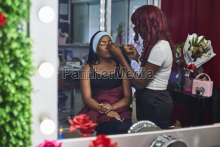 mirror image of visagiste applying makeup