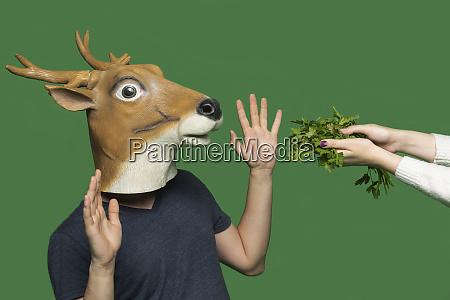 young man wearing deer mask raising