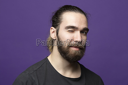 portrait of bearded young man winking