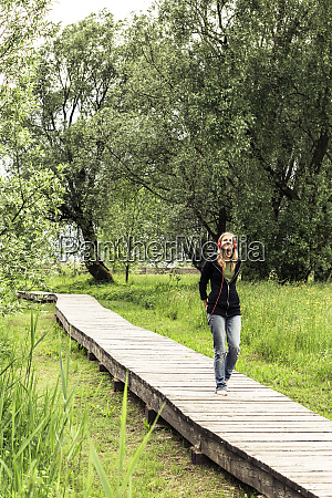 young woman with red headphones walking