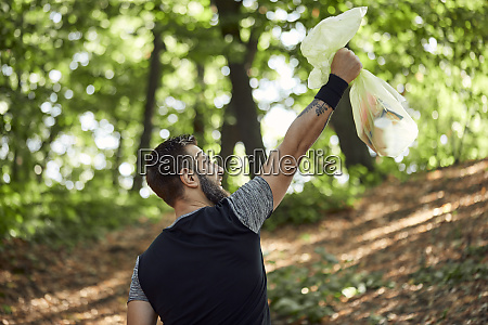 sporty man holding litter bag in