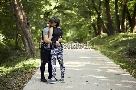 sporty couple hugging on forest path