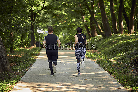 rear view of sporty couple running