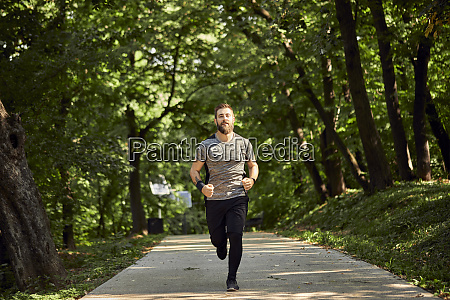 sporty man running on forest path
