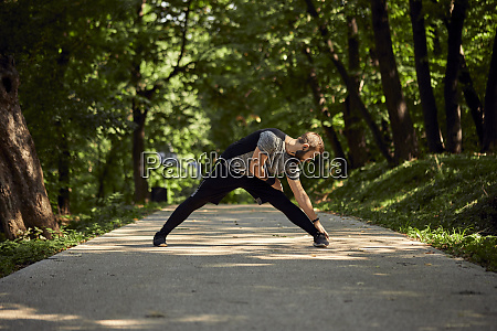 sporty man stretching on forest path