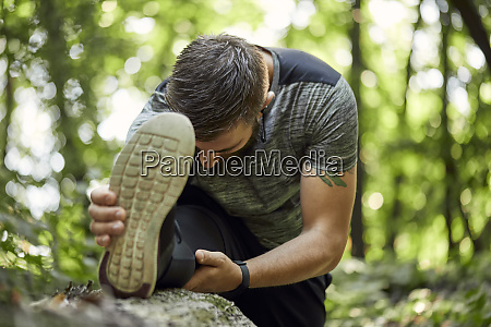 sporty man stretching in forest
