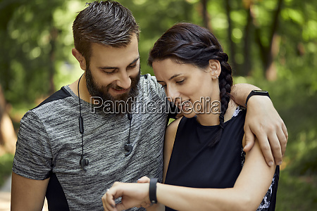 happy sporty couple checking smartwatch
