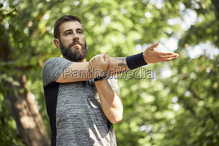 sporty man stretching in nature