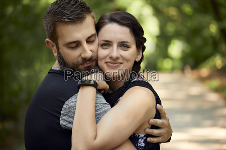 sporty couple hugging in forest