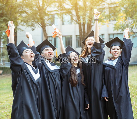 happy students in graduation gowns